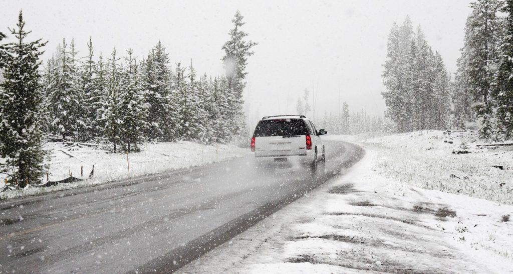 Voiture qui roule sur une route enneigée