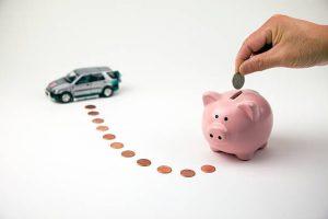 Tirelire rose en forme de cochon avec argent autour et figurine voiture