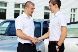 deux hommes se serrant la main devant une voiture
